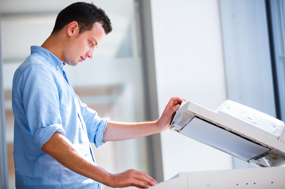 Handsome  young man using a copy machine (shallow DOF; color ton